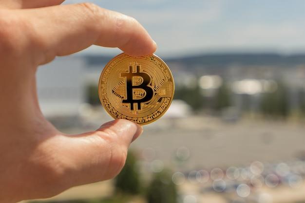 Пальцы человека держат большую круглую золотую монету биткойна перед промышленным городом.