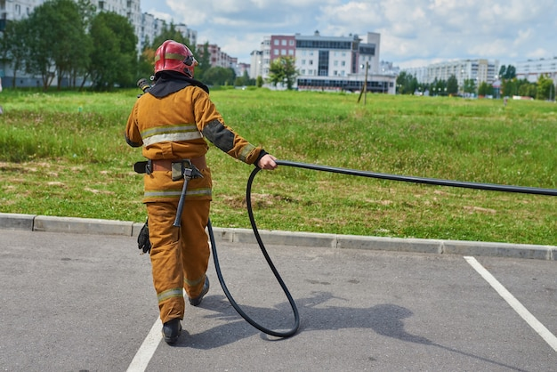 A man firefighter from a fire hose watering the grass