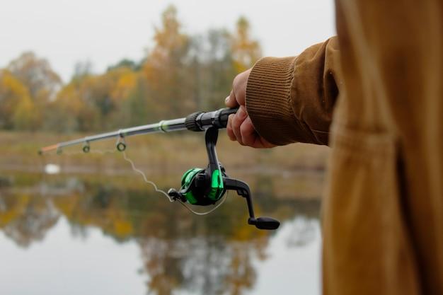 男の漁師は、森を背景に湖のリールで釣り竿で魚を捕まえます。