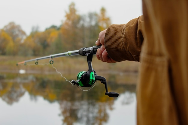 Man fisherman catches a fish on a fishing rod with a reel on the lake against the background of the forest.