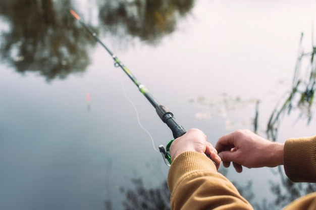 Man fisherman catches a fish on a fishing rod with a reel on the lake against the background.