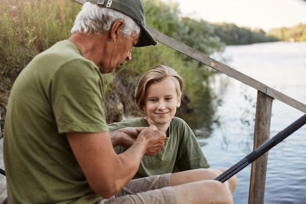 물고기를 잡는 방법으로 유명한 미끼를 연결하는 손자를 가르치는 남자 어부, 웃는 젊은 금발의 남자가 미소와 집중된 표정으로 수석 남성을 바라보고 물에 나무 계단에 앉아.