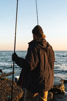 海岸で釣り竿と立っているコートを着ている男の漁師