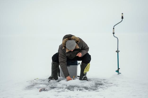Мужчина ловит рыбу в одиночестве на улице зимой