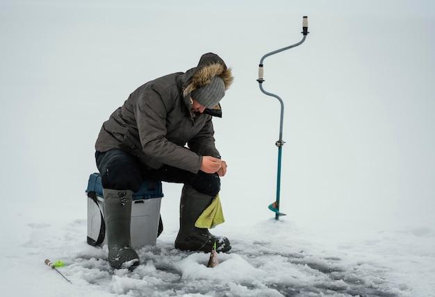 Uomo che pesca da solo fuori in inverno