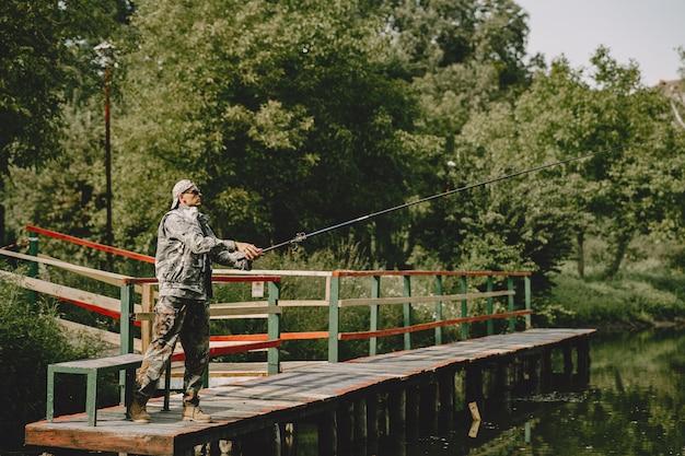 Мужчина ловит рыбу и держит удочку