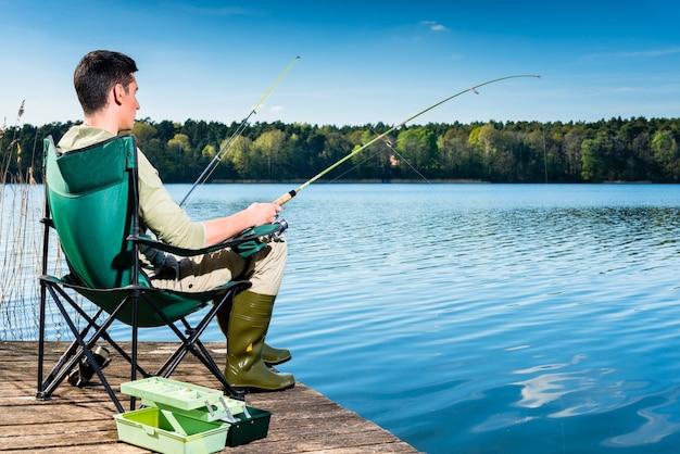Человек, ловящий рыбу на озере, сидя на пристани рядом с водой