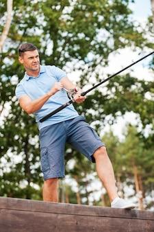 Человек на рыбалке. уверенный молодой человек, ловящий рыбу, стоя на набережной
