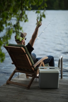 夏にフィンランドの湖のコテージ近くの木造桟橋から釣りをする男
