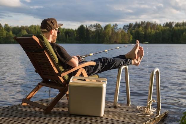 Мужчина ловит рыбу с деревянного пирса возле коттеджа на озере в финляндии летом