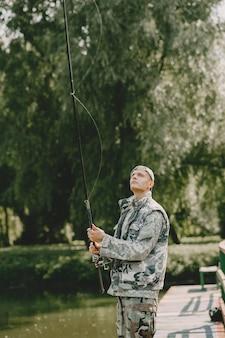 L'uomo pesca e tiene la canna da pesca