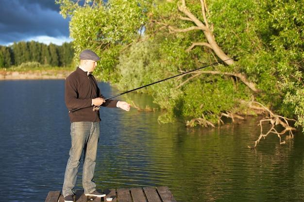 Человек, ловящий рыбу в пруду в солнечный день