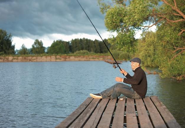 Человек, ловящий рыбу в пруду
