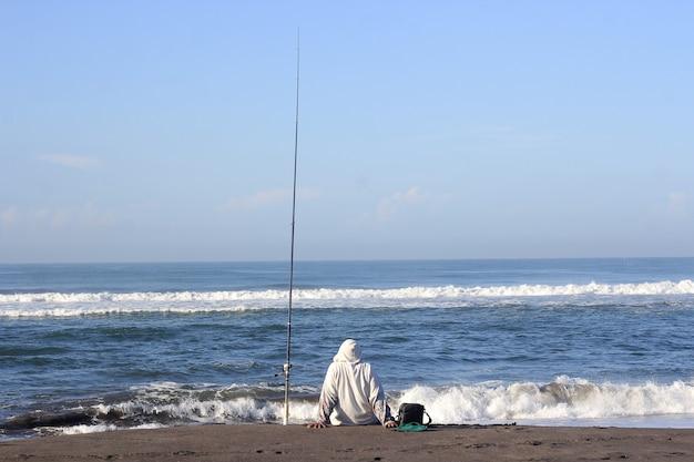 ビーチから海で釣りをする男
