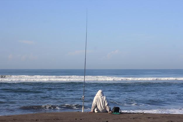 Человек, ловящий рыбу в море с пляжа