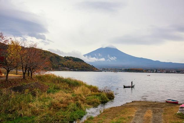 富士山を背景に河口湖でボートに乗って釣りをする男、