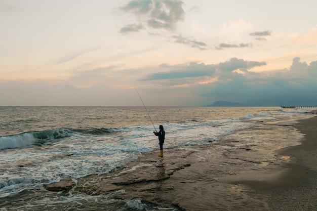 Man fishing on the sea shore