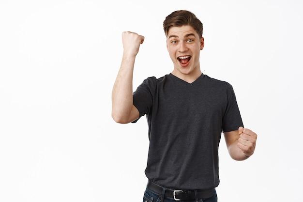 男拳ポンプ、はいと言って興奮しているように見え、勝利と祝い、勝利から勝利し、勝利の味を楽しみ、唱え、白の上に立つ
