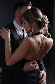 A man in a fit of passion unbuttons the dress of a young woman who embraces him