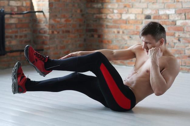 男のフィットネストレーニング。自宅でストレッチをしている上半身裸の男