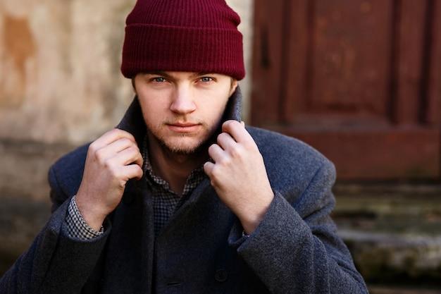 Человек фиксирует свой воротник в красной шляпе