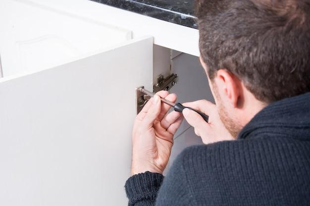 Мужчина чинит шкаф с помощью отвертки