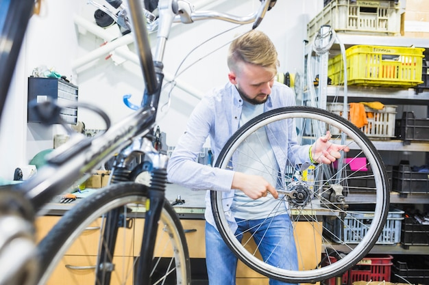 Man fixing bicycle tire with wrench in workshop