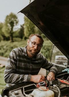 Man fixing a car outdoors auto repair service