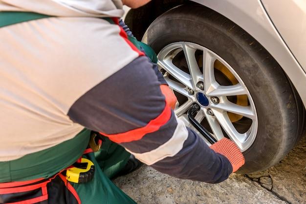 スパナで車のホイールを固定する男クローズアップ