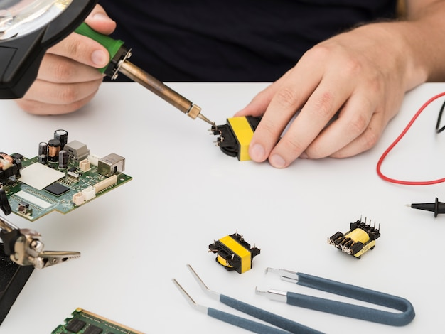 Man fixing a connector using the soldering iron