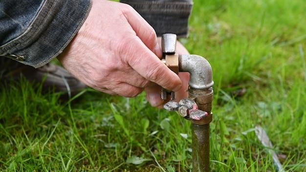 庭の水道管を固定する男。