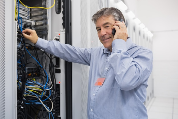 Man fixing server wires and talking on phone