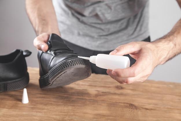 接着剤で靴を固定する男。