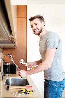Мужчина чинит кран гаечным ключом на кухне