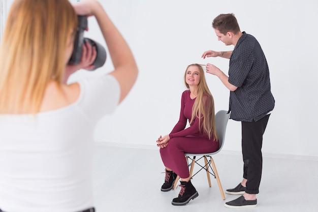 スタジオでモデルの髪型を修正する男