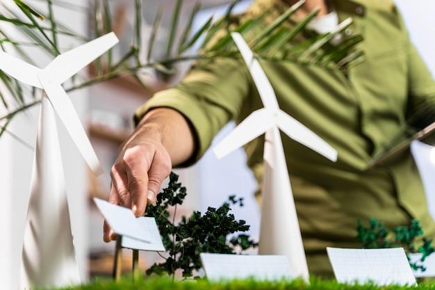 Uomo che fissa un layout di progetto di energia eolica ecologico