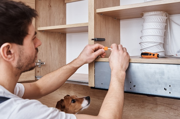Man fixing wire in kitchen cabinet with dog