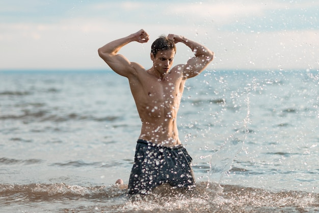 Man flexing his biceps in water