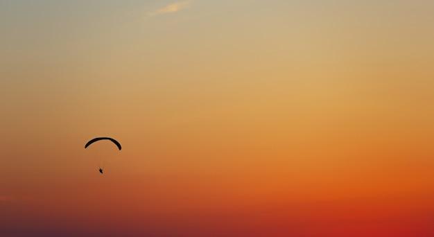 일몰 cloudless 하늘에서 패러 글라이더에 남자 비행.