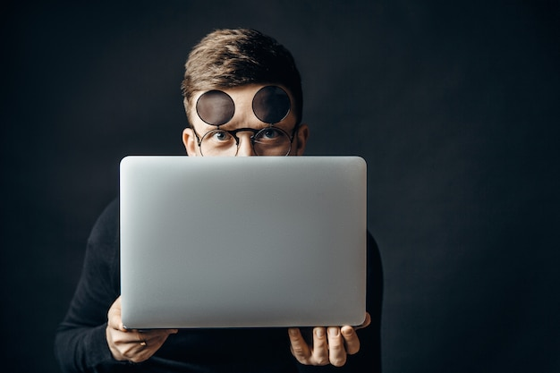Man in flip glasses hiding behind laptop