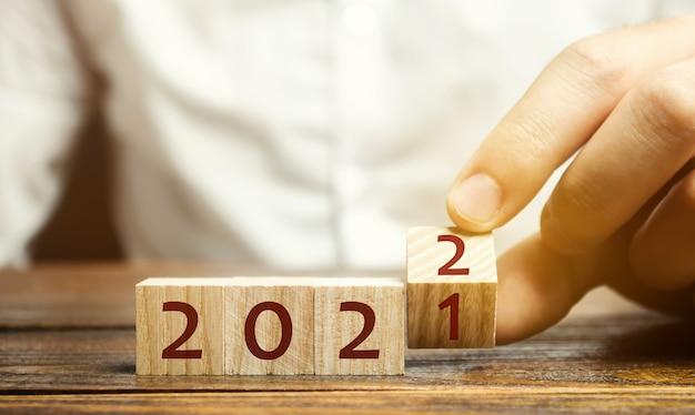 남자는 2021 년에서 2022 년까지 변화하는 블록을 뒤집습니다. 새해가 시작됩니다. 휴일과 크리스마스