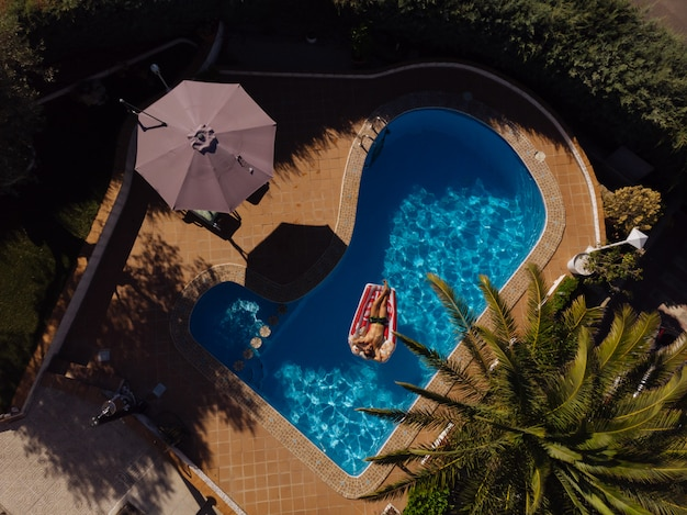 Man on floating mattress in swimming pool of a villa house