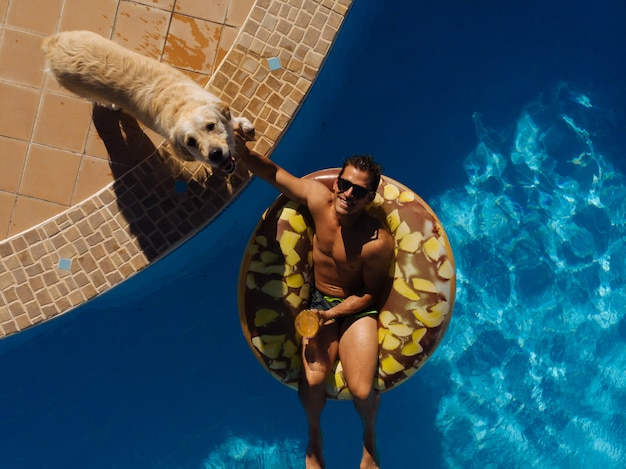 Man on floating ring in swimming pool of a villa house