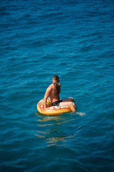 A man floats on an inflatable ring in the sea with blue water. vacation at the sea on a sunny day. turkey vacation concept. selective focus