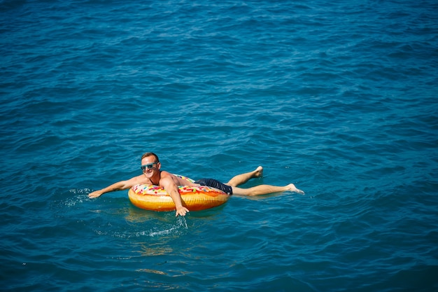 A man floats on an inflatable ring in the sea with blue water. vacation at the sea on a sunny day. turkey vacation concept