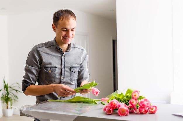 男性の花屋は赤いチューリップの花束を作り、木製のテーブルにパックで包みます。フラワーズ
