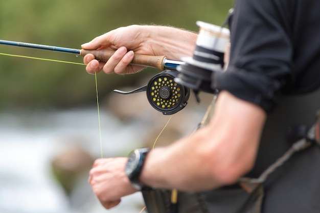 Man fly fishing with reel and rod. sport fly fisher man close up on reel.