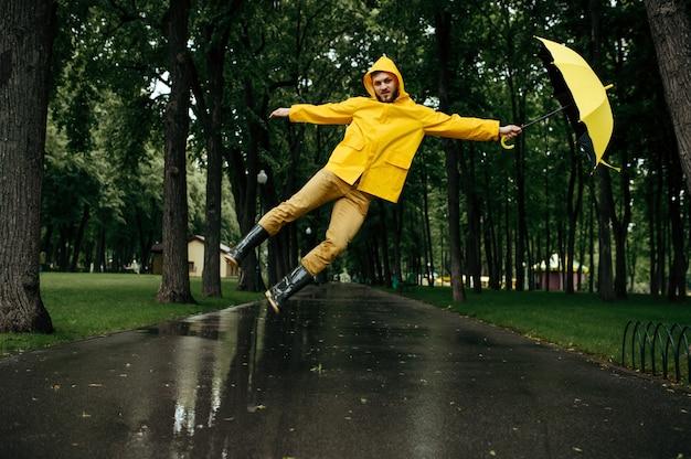 風の強い雨の日に夏の公園で傘を持って飛んでいる男。レインケープとゴム長靴の男性、路地の雨天