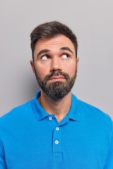 L'uomo focalizzato sopra considera che qualcosa ha i capelli scuri indossa una maglietta blu casual isolata su gray