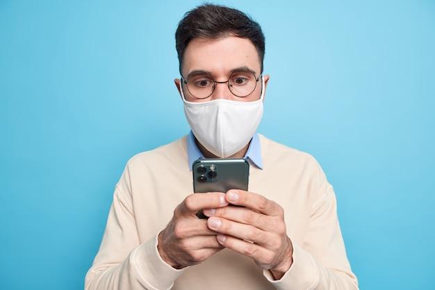 휴대형 디스플레이에 놀란 남자는 둥근 안경을 쓰고 캐주얼하게 옷을 입고 스마트폰을 통해 뉴스 피드를 확인합니다.